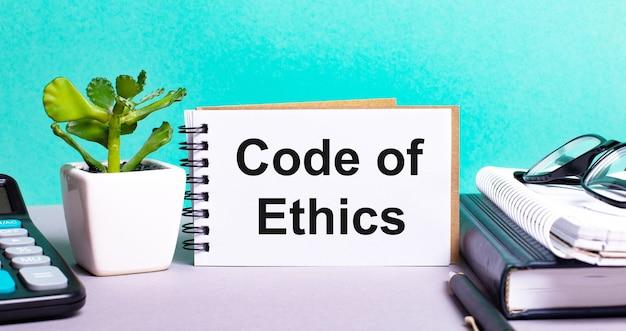 Code d'éthique est écrit sur une carte blanche à côté d'une fleur en pot, des agendas et une calculatrice. concept organisationnel