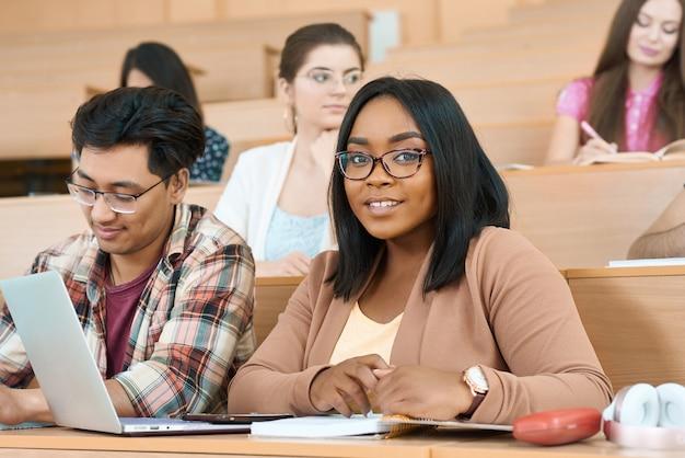 Les coéquipiers apprennent à l'université, une fille regarde la caméra.