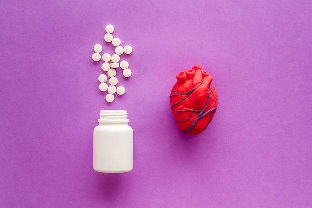 Coeur anatomique humain en pâte à modeler avec des pilules traitement cardiaque