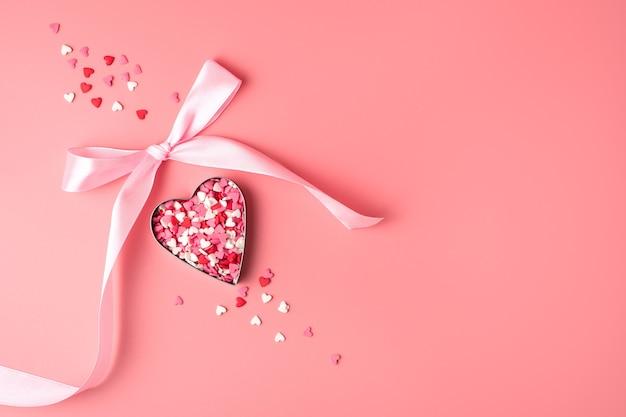Coeur avec un arc sur fond rose.