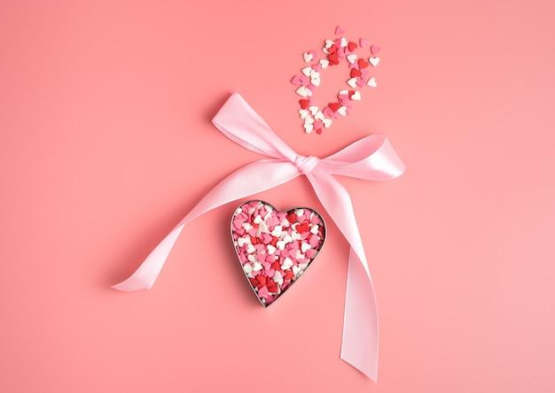 Coeur avec un arc en forme de jouet suspendu sur fond rose. la vue du haut. le concept de la saint-valentin.