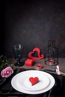 Coeur sur des assiettes avec rose et bougies