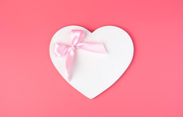 Coeur blanc avec un arc festif sur fond rose.