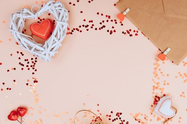 Un coeur blanc en bois et une enveloppe avec un ruban rouge près de perles avec des coeurs sur des couleurs rose pastel.
