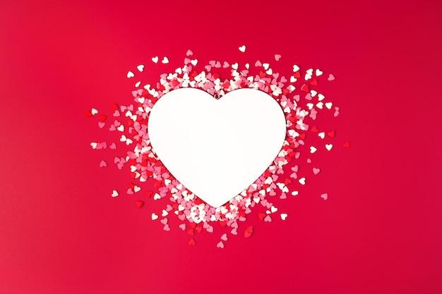 Coeur blanc et confettis colorés sur fond rouge. vue de dessus