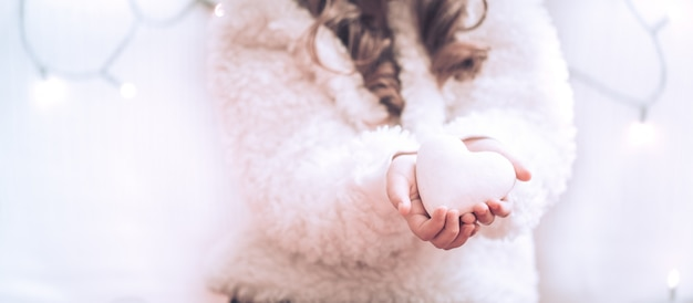 Coeur blanc entre les mains d'une petite fille