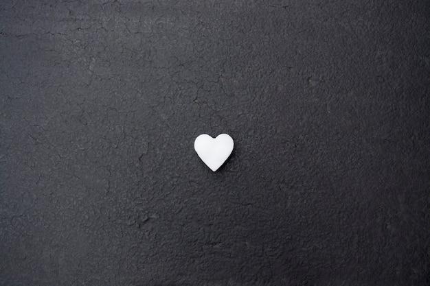 Coeur blanc fait de neige portant sur fond de béton noir