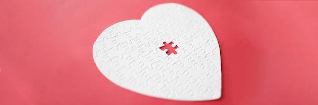 Coeur blanc fait de puzzle allongé sur fond rouge