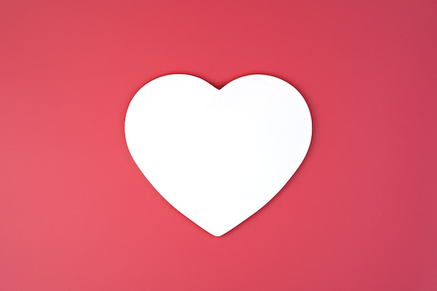 Coeur blanc sur fond rose.