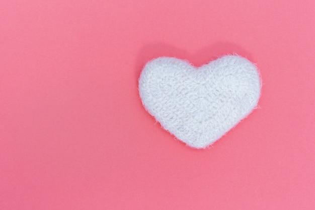 Coeur blanc moelleux sur fond rose. peluche en forme de coeur. concept d'amour. le minimalisme.
