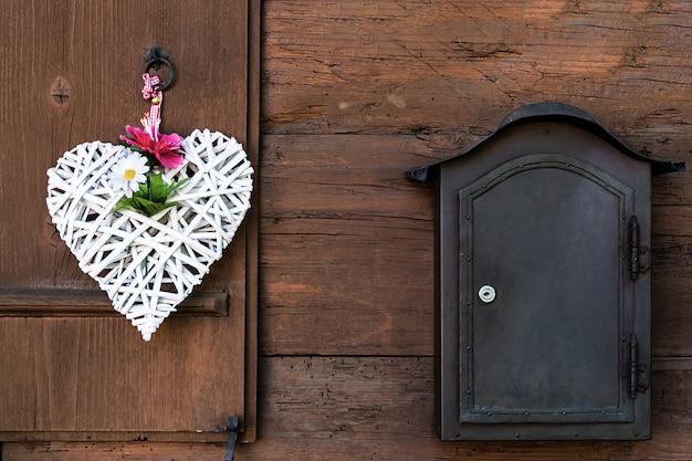 Un coeur blanc en osier avec pivoines et marguerites est suspendu à un volet en bois et à une boîte aux lettres à côté.