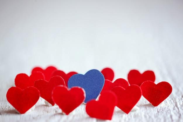 Coeur bleu et beaucoup de coeurs rouges sur fond blanc. valentin