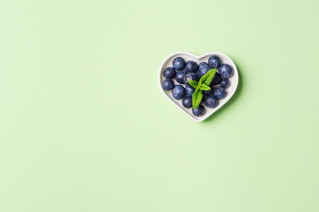 Coeur de bleuets frais sur vert pastel