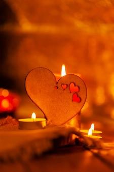 Coeur en bois et bougies. carte de voeux saint valentin avec bougie et coeur. concept d'histoire d'amour