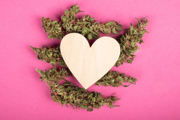 Coeur en bois sur les bourgeons de marijuana sur fond rose, espace de copie de symbole d'amour et de la saint-valentin.