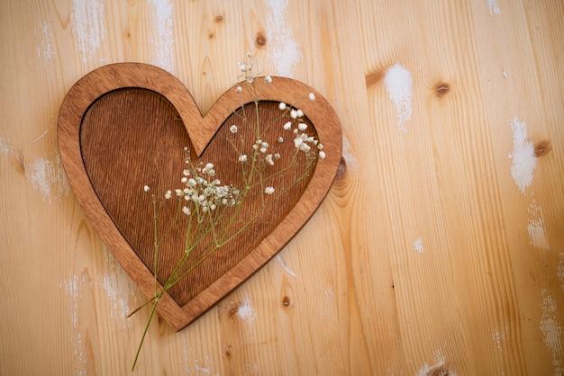 Coeur en bois avec un brin de petites fleurs blanches