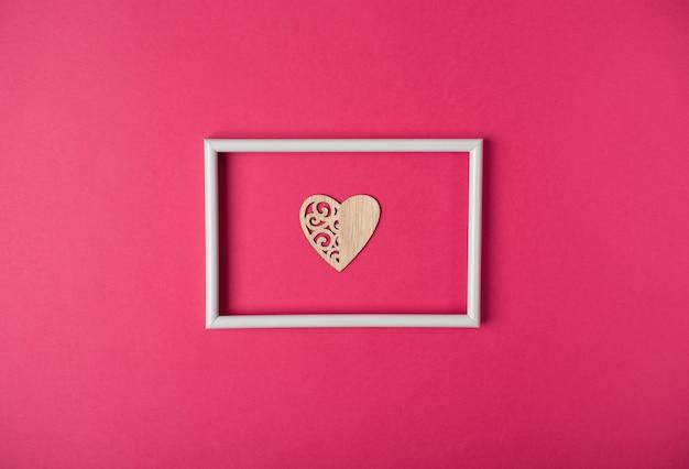 Coeur en bois dans le cadre blanc sur le fond rose chaud. concept de la saint-valentin.