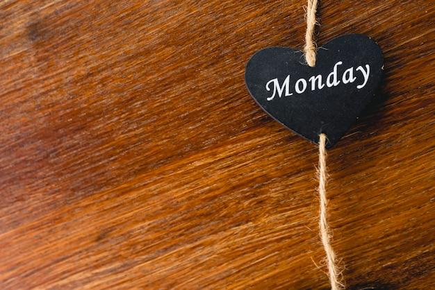 Coeur de bois noir avec le jour de la semaine écrit dessus, lundi.