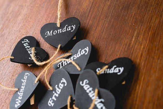 Cœur de bois noir sur lequel sont écrits les jours du week-end.