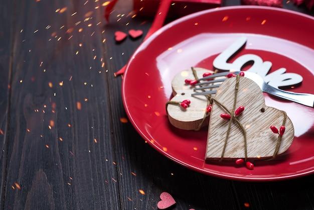 Coeur en bois sur plaque rouge pour la saint valentin avec concept de l'amour pour la saint valentin