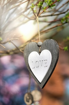 Coeur en bois avec quatre lettres sculptées sur l'arrière-plan flou. symbole d'amour. concept de la saint-valentin