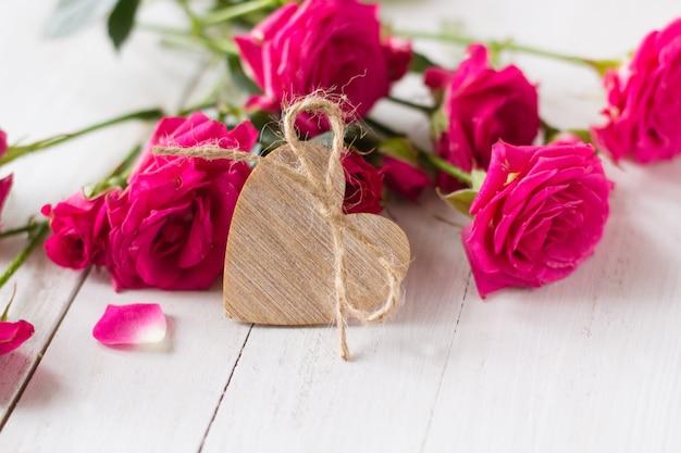 Coeur en bois et roses roses sur un tableau blanc en bois pour la saint valentin
