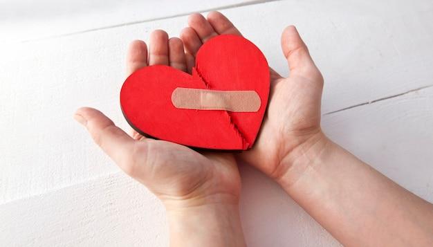 Le coeur en bois rouge brisé dans les mains de la femme