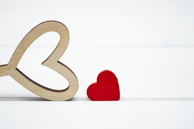 Coeur en bois rouge et creux sur un fond en bois blanc