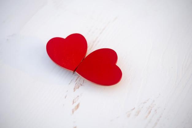 Coeur en bois rouge sur un plancher en bois blanc, floue exprime l'amour festival d'amour festival de valentine, bannières, cartes postales en ligne