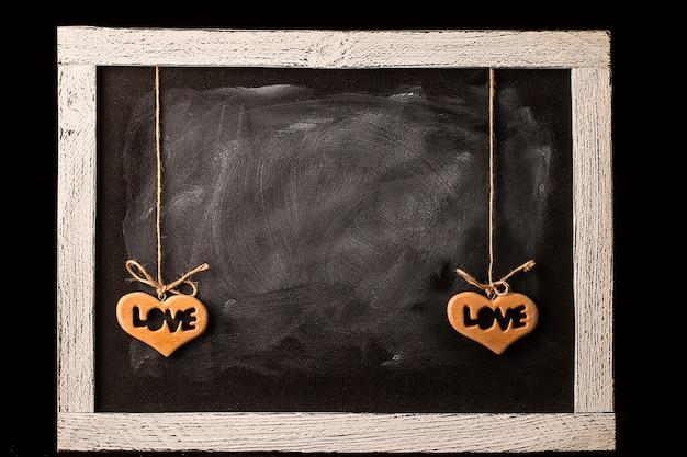 Coeur en bois sur tableau noir dans la chambre sur fond noir