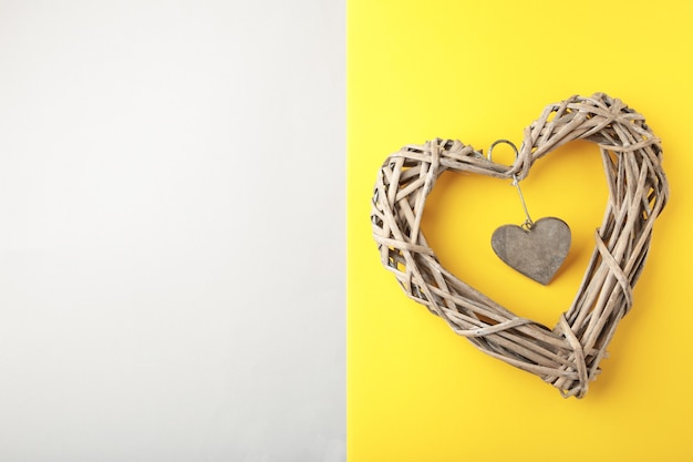 Coeur en bois tissé sur fond jaune et gris.
