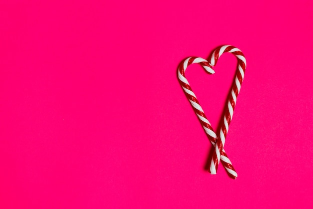 Coeur de bonbons de noël sur fond rose