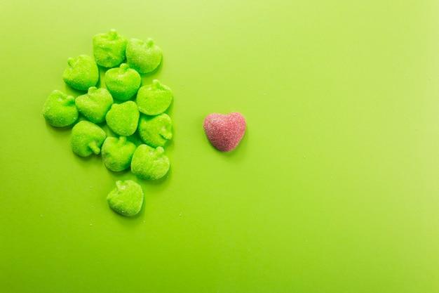 Coeur de bonbons près de tas de pommes gelées