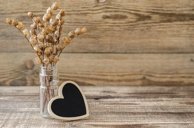 Coeur avec un bouquet de fleurs séchées sur un fond de bois