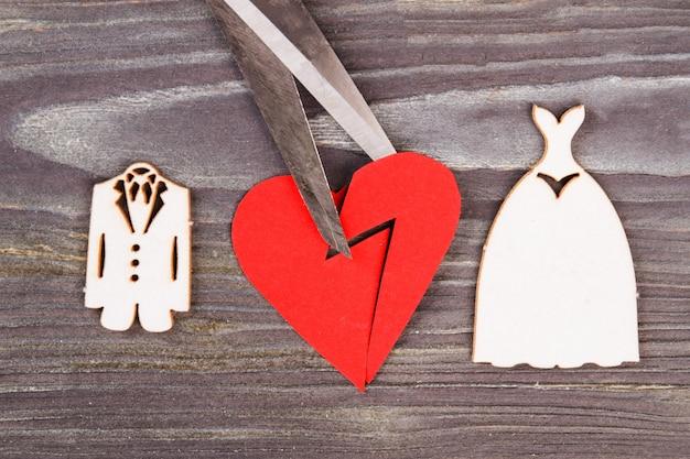 Cœur brisé avec des ciseaux. concept de divorce et de chagrin. fond de bois gris.