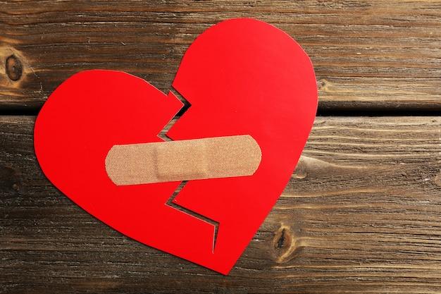 Coeur brisé avec du plâtre sur une surface en bois