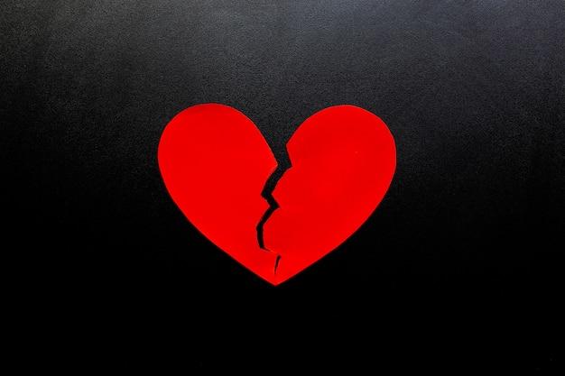 Coeur brisé en papier rouge sur fond noir, représente l'amour.