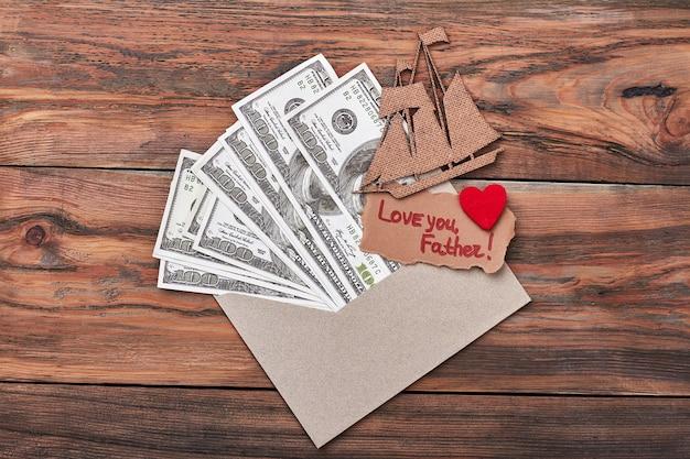 Coeur sur carte près de l'argent. navire en aggloméré sur enveloppe. père présent avec croisière.