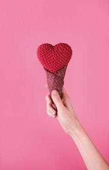Coeur de chiffon dans une tasse de gaufre dans une main sur un fond rose