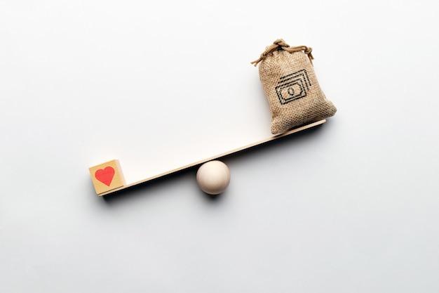 Coeur comme symbole d'amour avec un sac d'argent sur la balance. priorité d'amour.