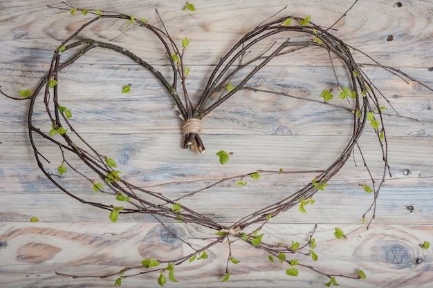 Cœur composé de branches de bouleau avec des feuilles fraîches sur une table en bois