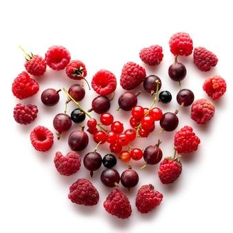 Cœur composé de différentes baies fraîches comme symbole de l'amour pour le concept de nourriture végétalienne saine et crue