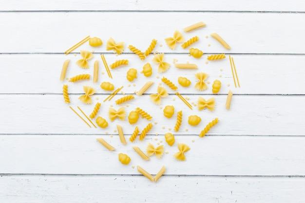 Cœur composé de différents types de pâtes sur une table en bois