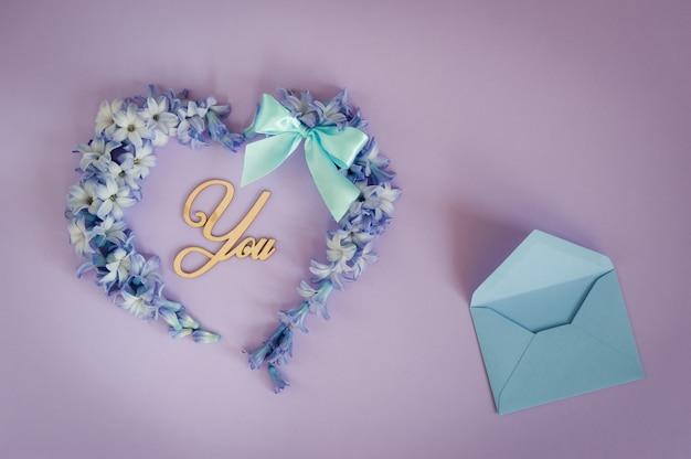 Cœur composé de fleurs en jacinthe avec noeud à la menthe et lettres en bois sur fond violet.