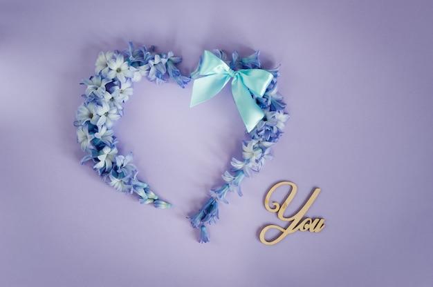 Cœur composé de fleurs de jacinthes et d'un nœud menthe sur fond violet.