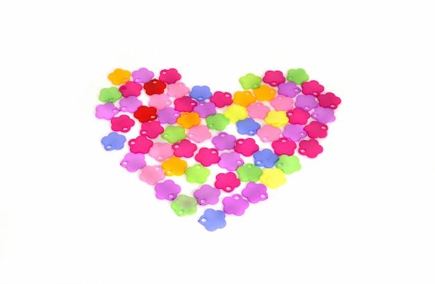 Cœur composé de fleurs en plastique colorées