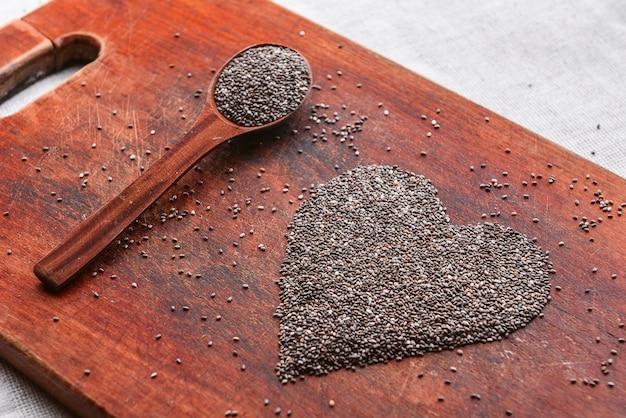Coeur composé de graines de chia sur une table en bois. concept de santé et de saine alimentation