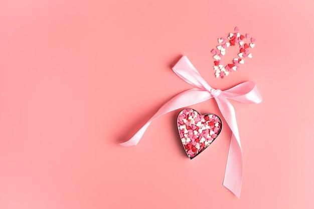 Coeur de confettis avec noeud sur fond rose. vue de dessus avec espace pour copier. concept 14 février.