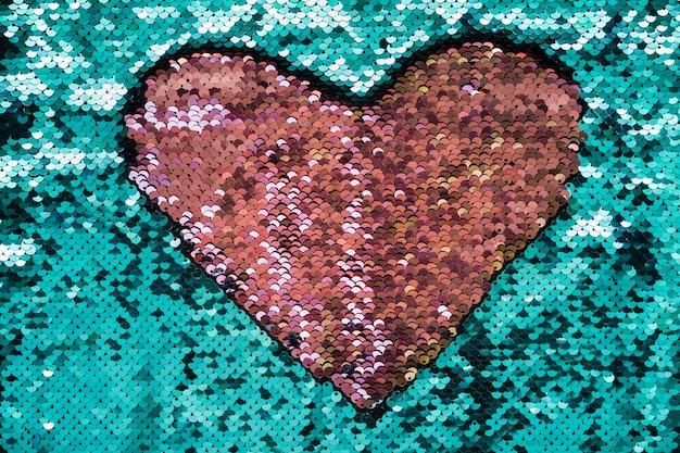 Coeur de corail en paillettes sur turquoise.