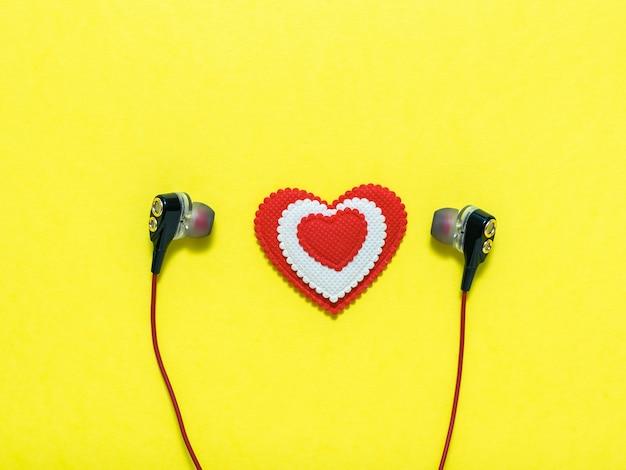 Coeur de couleurs blanches et rouges dans les écouteurs sur fond jaune